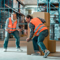 die-schutzprofis-stock-photo-warehouse-workers-moving-boxes-mehr-leistung